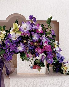 """Summer Wedding Themes: Bold and Bright """"Climbing Clematis: This sweeping creation is a twist on the pageant (or presentation) bouquet, named for the long-stemmed arrangement a beauty queen carries in the crook of her arm. It is 18 inches long and consists of hellebores, clematis, gladiolus, forget-me-nots, and sweet peas. Its grand dimensions are ideal for a formal occasion; for a more casual event, try paring down the size."""""""