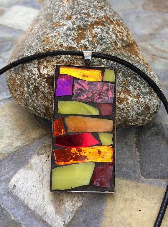 This handmade, one-of-a-kind mosaic jewelry pendant features hand-cut red, yellow, and orange stained glass, as well as red van gogh glass. Black grout was used to bring out the colors. Grout sealant was used to protect this work of art. The pendant features a rectangular bezel tray