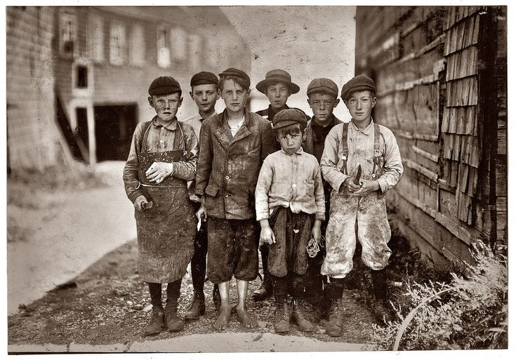 U.S. Cutting crew, 1911. Eastport, Maine. All these boys are cutters in the Seacoast Canning Co., Factory #7. Ages range from 7 to 12. Seven year old boy in front, Byron Hamilton, has a badly cut finger, but helps his brother regularly. Behind him is his brother George, 11 years. He cut his finger half off while working. At times they start at 7 A.M. Work all day, and until midnight, but the work is very irregular. // Photograph by Lewis Wickes Hine.