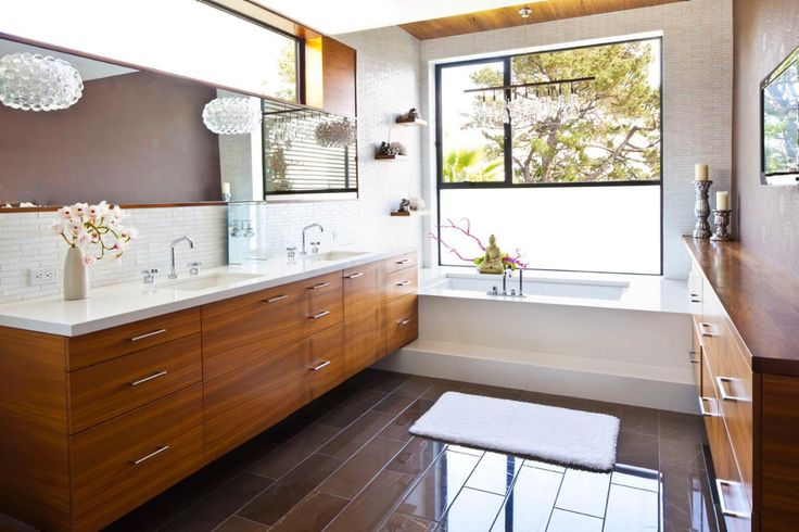 Fresh white tiles and crisp, sharp lines create a clean aesthetic in this spacious bathroom. A long, midcentury modern vanity lends warmth to the space, and a large window keeps the room feeling airy.