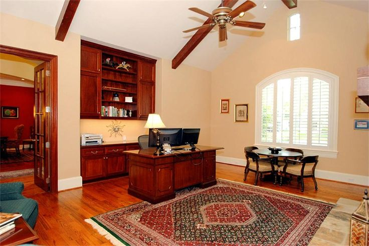 Another view of private study shows built-in filing cabinets & shelves, neutral decor, and custom blinds.