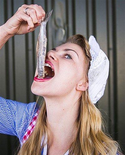 A woman eats a 'Hollandse Nieuwe' herring, in Scheveningen, the Netherlands, on June 11 (© Remko de Waal/AFP/Getty Images)