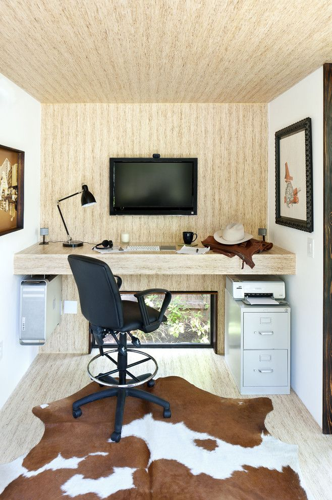 brown hoem office with light brown flooring up to the wall up front, table, wall mounted screen, black chair, grey cabinet, painting, cow skin patterned rug of Home Office Decoration for Crisp yet Comfortable Ambiance