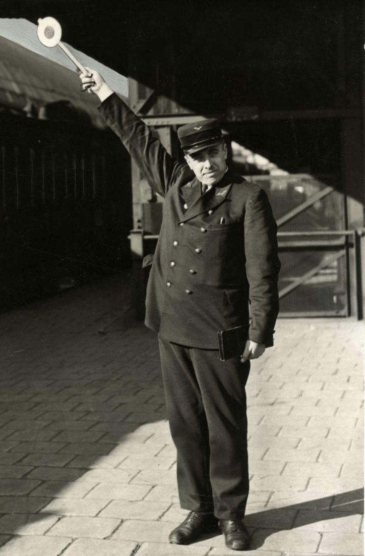 De perronchef staat klaar met de 'pannekoek' omhoog: de trein kan vertrekken. Zonder plaats en datum. - Het Geheugen van Nederland - Online beeldbank van Archieven, Musea en Bibliotheken