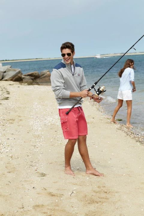 a cute guy wearing a Vineyard Vines fleece and pastel shorts while he is fishing on the beach and laughing naturally. NOW THAT'S MY KIND OF GUY.