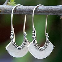 Sterling silver hoop earrings, 'Hollow Bell' Outlined in silver, sterling bells become graceful earrings. Wadarat Supasirisuk's original design combines contemporary Thai style and classic Eastern motifs.