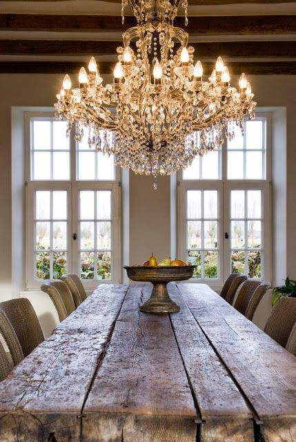 Loving this mix of a rustic plank dining table with an ornate crystal chandelier