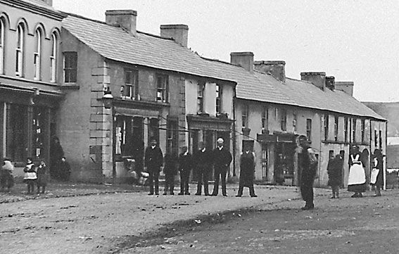 Main Street before the First World War was still unpaved and had to be sprayed by a water cart to keep down the summer dust. On the left the buildings which were Calvert's Chemist can still be recognised. To the right behind the girls in aprons is the arch leading to McConnell's yard