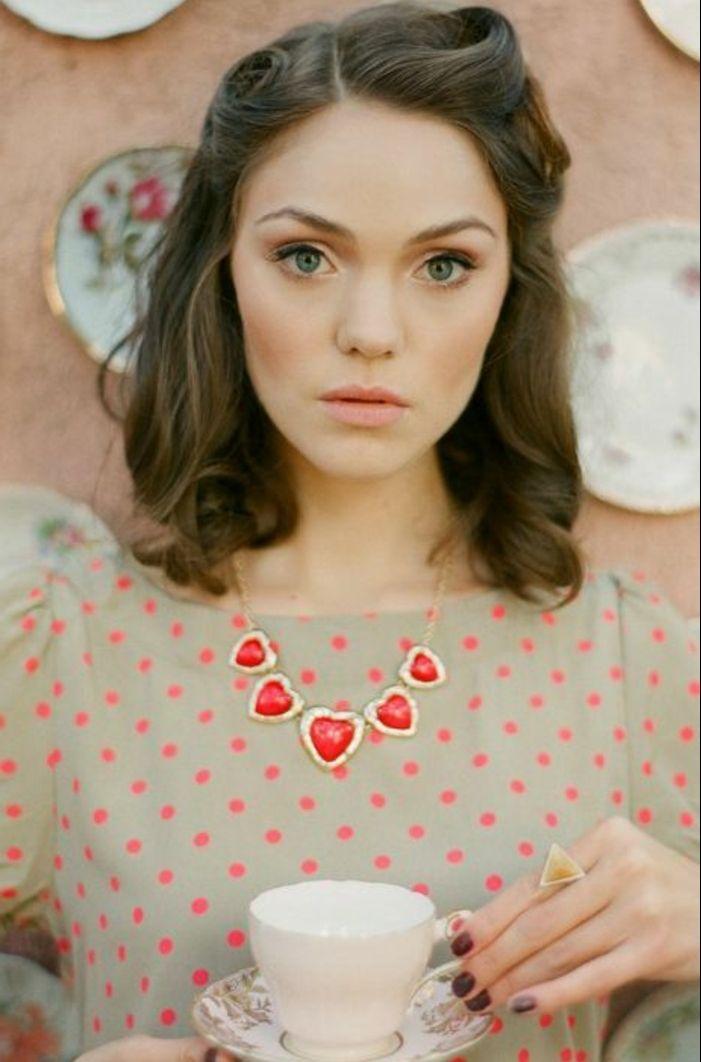 coiffure vintage, robe à points rouge, collier en or, manucure bordeaux, tasse de thé