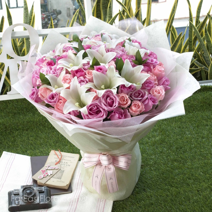PT28 - Grandiose Pink  Stately white trumpet lilies are like heaven's stars in a grandiose cloud of pink roses. This dramatic scenery is framed in a glittery cream backdrop and finished off elegantly with a pink ribbon. It is an arrangement that surely rises to the occasion!
