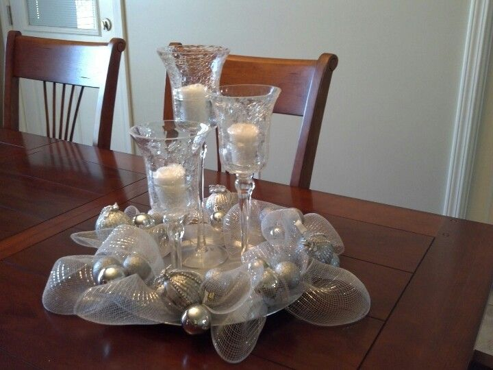 A silver charger plate with random drilled holes with a very small drill bit.  Inserted pipe cleaners into the holes and tied on deco mesh and balls.  Placed 3 cracked glass sconces.