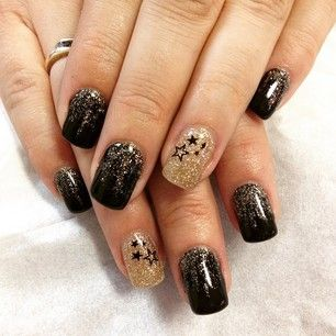 Black and gold are traditional New Year's Eve colors, but you can add star embellishments to make them feel fresh. | 23 Ideas For Amazing New Year's Eve Nails