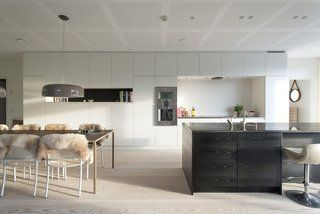 Built-in kitchen cabinets and a monolithic island help keep the space uncluttered in this beautiful modern Scandinavian kitchen. The wall ovens are from Gaggenau.
