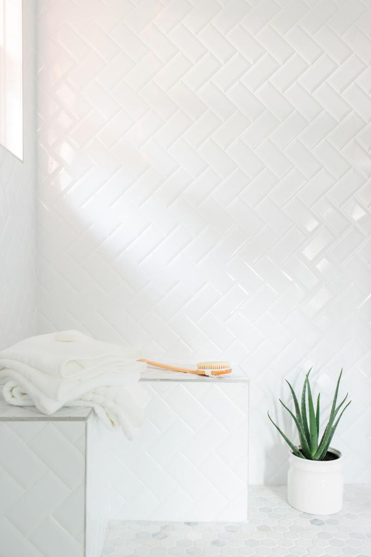 An inexpensive alternative to more pricey tiles, simple subway tiles were installed in a herringbone pattern in the shower. White grout between the tiles lends a more cohesive look.
