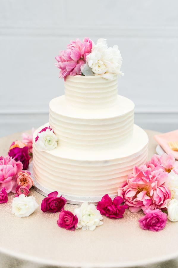 Three tier pink flower topped wedding cake: http://www.stylemepretty.com/massachusetts-weddings/cape-cod/2017/01/10/a-romantic-farm-wedding/ Photography: Leila Brewster - http://leilabrewsterphotography.com/