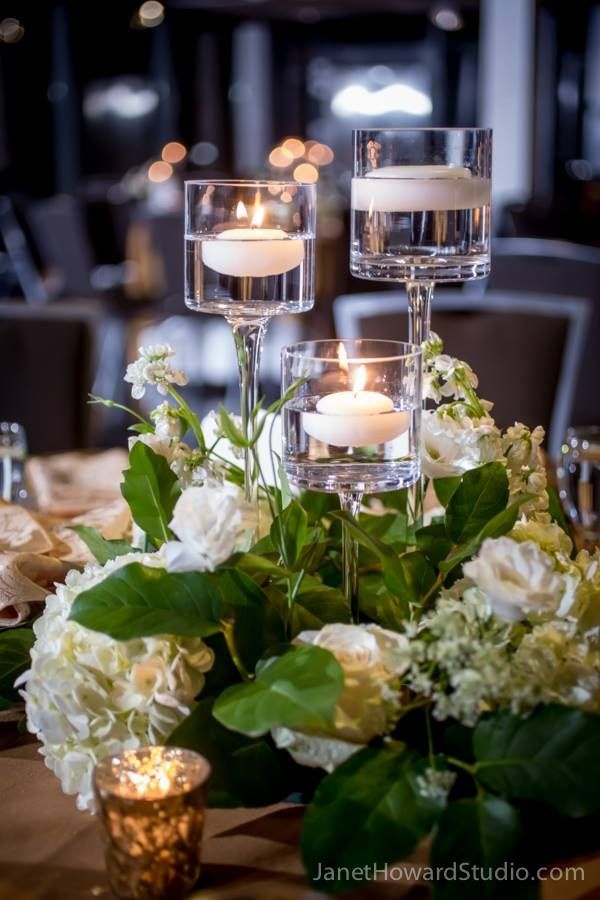This table arrangement features different sizes of wine glass pillars with floating candles. The pillars are surrounded by white hydrangea, white stock, pink roses, salal, white lisianthus, and queen anne's lace.