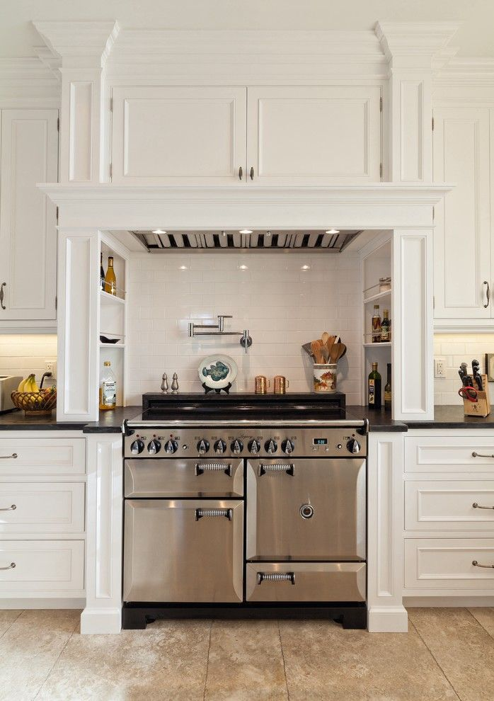 Elegant pot filler faucet in Kitchen Traditional with Water Spigot Above Stove next to Built In Range Hood alongside Legacy Cabinets and Shaker Crown Molding