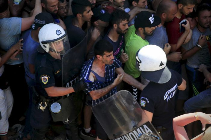 A migrant argues with a riot police officer on the Greek island of Kos