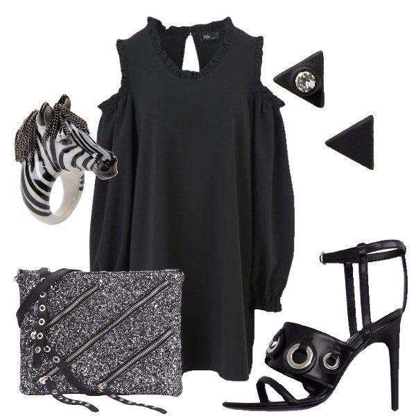 Outfit composto da vestito nero con maniche lunghe che lasciano, però. scoperte le spalle, sandali alti con cinturino alla caviglia, pochette glitterata, anello a forma di zebra e orecchini a forma di triangolo.