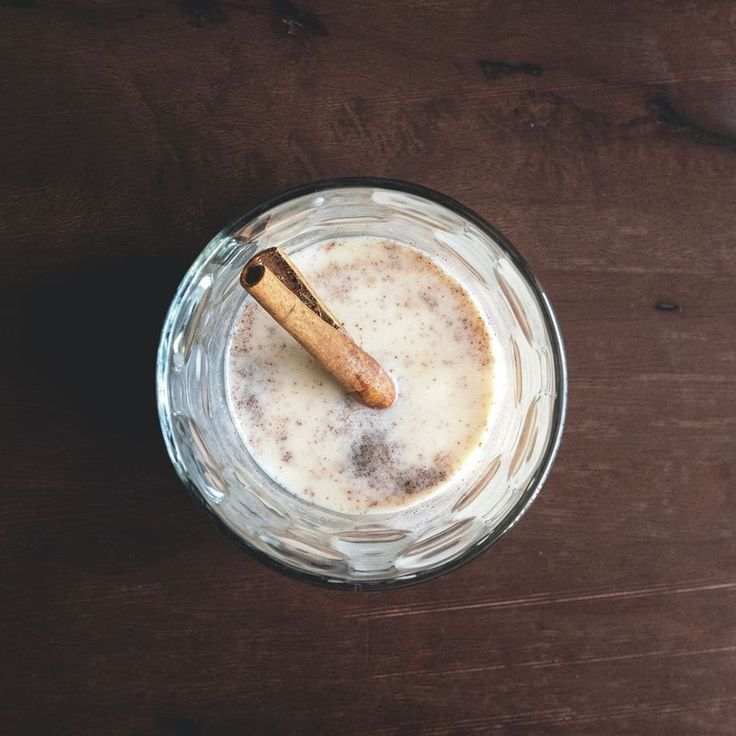 Directly Above Shot Of Coquito With Cinnamon In Glass On Wooden Table