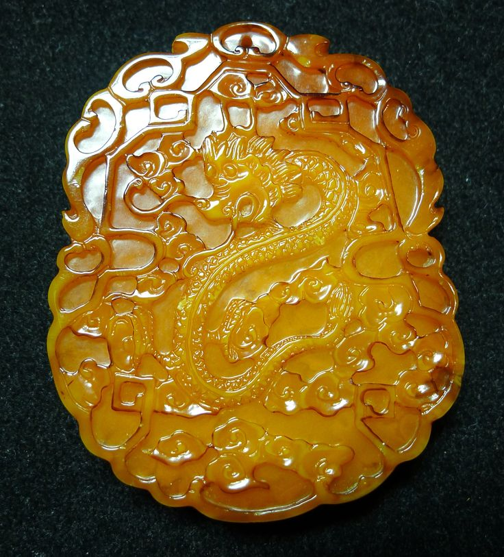 Amber plaque, a dragon and cloud motif in centre. 18th c Qing period.
