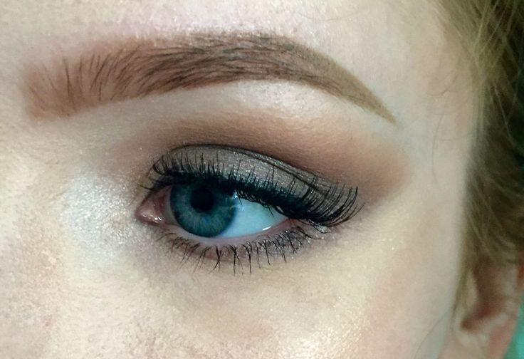 Smokey, shimmery taupe eye makeup with winged lashes.