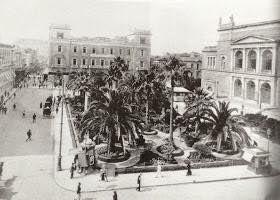 η πλατεία που δεν υπάρχει σήμερα, όπως δεν υπάρχει και το κτήριο στο δεξιό μέρος της φωτογραφίας του 1925. Και όμως και τα δύο ήσαν στο κέντρο της Αθήνας και καταλάμβαναν μεγάλο μέρος από την πλατεία τότε Λουδοβίκου, Λαού μετά Κοτζιά και σήμερα Εθνικής Αντιστάσεως