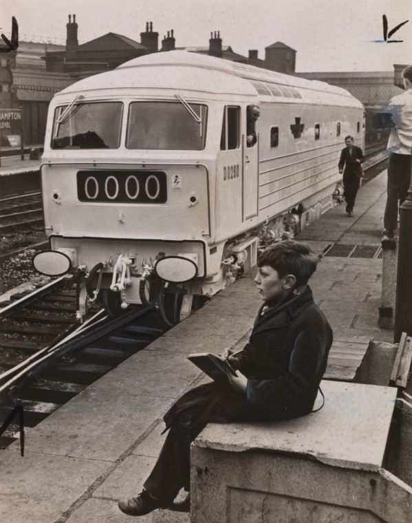 A photograph entitled 'Young train spotter at station with the ghost train in background', taken in April 1962 by an unknown photographer for the Daily Herald.    The train in the photograph is the D0260 'Lion', built in 1962 by the Birmingham Railway Carriage and Wagon Company. 13 year old Michael Spooner had spotted the 'ghost train' on its trial run from Birmingham to Shrewsbury.