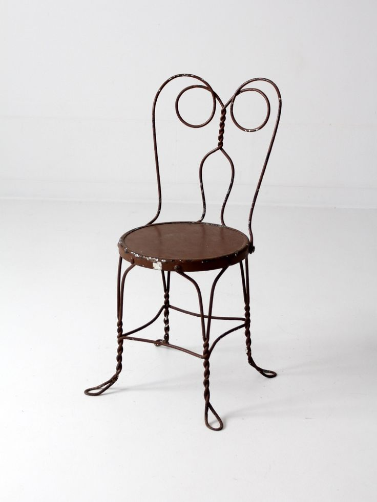 A vintage ice cream parlor chair. The brown metal chair features a classic