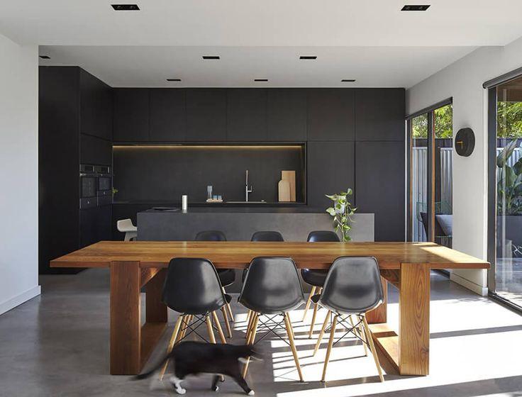 Cozinha masculina com armários pretos, balção de cimento queimado e móveis de madeira.