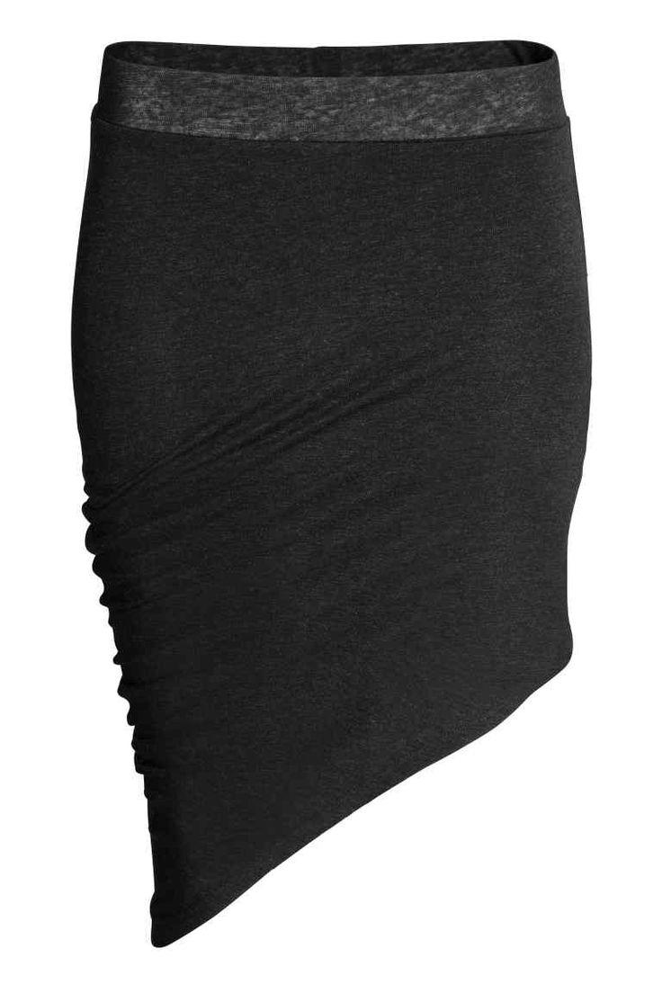 Falda asimétrica: Falda corta en punto de viscosa con lino en la trama. Modelo con cintura elástica y bajo asimétrico que crea un efecto drapeado en un lateral. Enagua corta de tela.