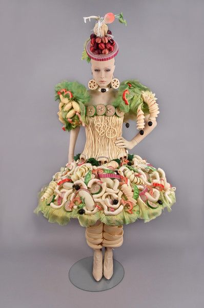"""WILLA KIM/ BARBARA MATERA PASTA SALAD ENSEMBLE, 1988 Created for a Regina Wine Vinegar """"Best Dressed Salad TV ad. Dress with hoop skirt, corset bodice, 3D pasta shapes and vegetables in satin, lycra and foam, tights, ruffled panties, knee-high fusilli leggings, pasta earrings, olive choker, hat with vegetables. Together with a pair of white leather high heel booties. Label: Barbara Matera, Ltd."""