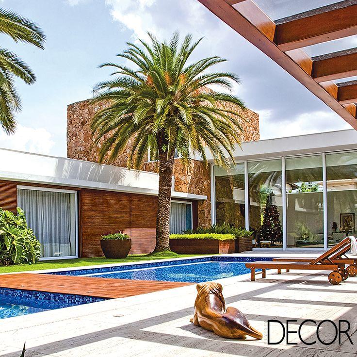Projeto paisagístico assinada por Marcelo Bellotto destaca layout clean e equilibrado com diversas plantas, palmeiras e árvores frutíferas contribuindo de forma graciosa para a arquitetura.