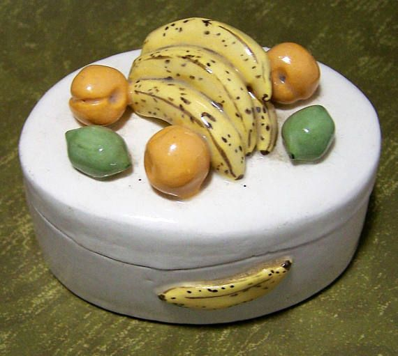 Vintage porcelain oval shape trinket box Hand made by Pennsylvania artist Has detailed bananas, peaches, and limes on lid and sides 3 1/4 x 2 1/4 inches, 2 1/4 inches high Unsigned, but purchased in PA in the 80s at a craft show Lovely detailing Good condition, gently owned, no