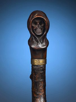 "The Grim Reaper Cane: This rustic cherry wood staff is topped by a carved walnut handle in the form of the ominous Grim Reaper. This haunting yet marvelously crafted walking stick is the perfect addtion to any well-rounded cane collection. Circa 1900 38 7/8"" length"