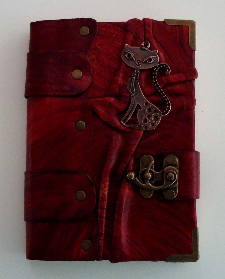 """""""Diario Misterio""""  Diario de diseño único, color rojo, hecho completamente a mano con piel genuina de la más alta calidad y con un pendiente de gatita en el frente."""