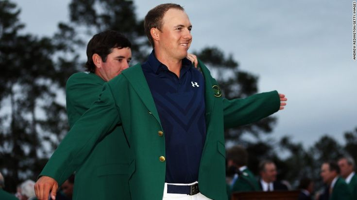 Defending champion Bubba Watson presents Jordan Spieth with the champion's green jacket after he won the 2015 Masters Tournament on April 12 in Augusta, Georgia.