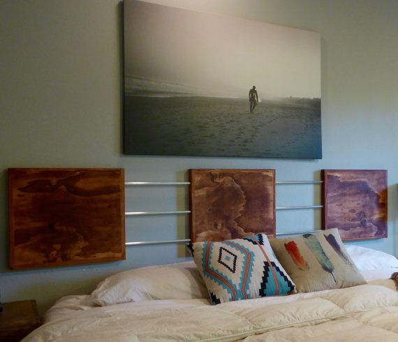 This Modern Headboard was handcrafted using three wooden panels connected by round aluminum tubing to create a contemporary, industrial design. The wooden panels have been sanded, stained, and varnished to enhance the natural beauty of the wood. The picture illustrates a Mahogany stain. This item can be modified to specific dimensions for any size bed and different stain options are available at check out. The dimensions of the illustration are as follows: Wood Panels: 20in x 18in x 1.5in…