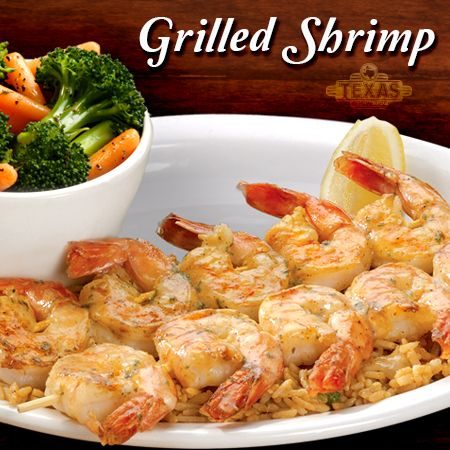 Two skewers of shrimp, seasoned and grilled, then drizzled with garlic lemon pepper butter and served over a bed of seasoned rice.