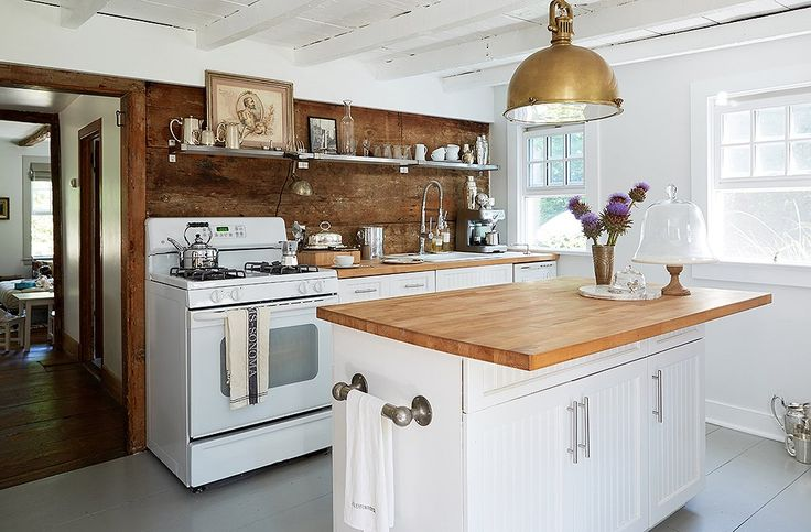 """The Millers' kitchen most recently had faux-granite countertops on maple cabinets. """"We just resurfaced [the countertops] with cheap Ikea butcher block, painted the cabinets, and changed the hardware."""""""