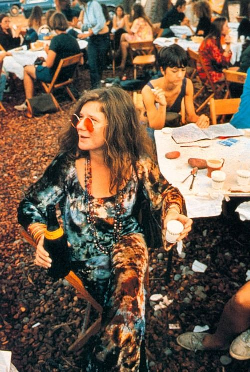 Janis Joplin pouring out some Champagne! Surprise! Surprise! It was said that she had nearly 10 hours to wait due to delays getting artists in and to weather before finally going on stage. Also I understand that her and a few other performers decided to stick around after their performances.