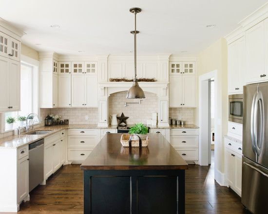 off white cabinets, dark island with butcher block top, subway tile backsplash, stainless steel appliances