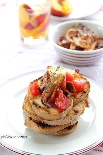 Bruschette con calamari grigliati, pomodori perini e olive taggiasche
