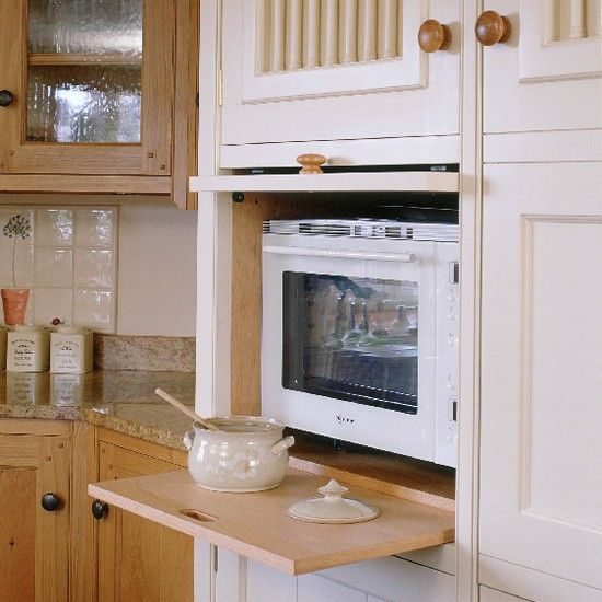 In a housekeeper's cupboard by Daedalian, a compartment for the Neff microwave has an up-and-over door and a pullout surface for hot dishes....