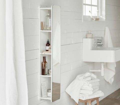 Pictures In Gallery A white wall mirror with shelves behind that stores bottles and creams