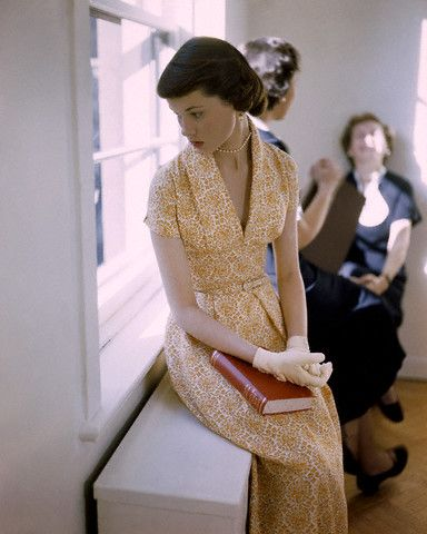 College student sitting by a window sill, 1949 color photo print ad magazine vintage image 40s 50s women in yellow dress gloves book day wear fashion style