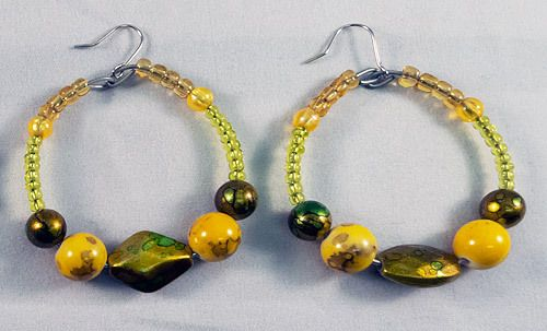These are beautiful circular earrings made with a mix of yellow and green beads. The earrings measure at 4.5 cm.