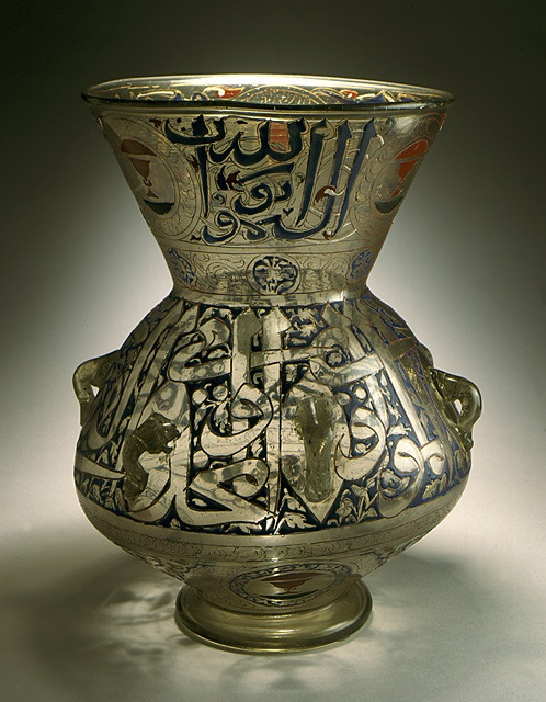 "A mid-fourteenth-century enamelled and gilded glass lamp from Egypt or Syria with Islamic ornamentation and calligraphy. The neck is inscribed with the first few words of a Qur'anic verse (24:35) that likens the light of God to the light yielded by an oil lamp: ""God is the Light of the heavens and of the earth.""; the base gives the name of the owner, Shaykhu al-Nasiri and his heraldic emblem. (LACMA Collections)"