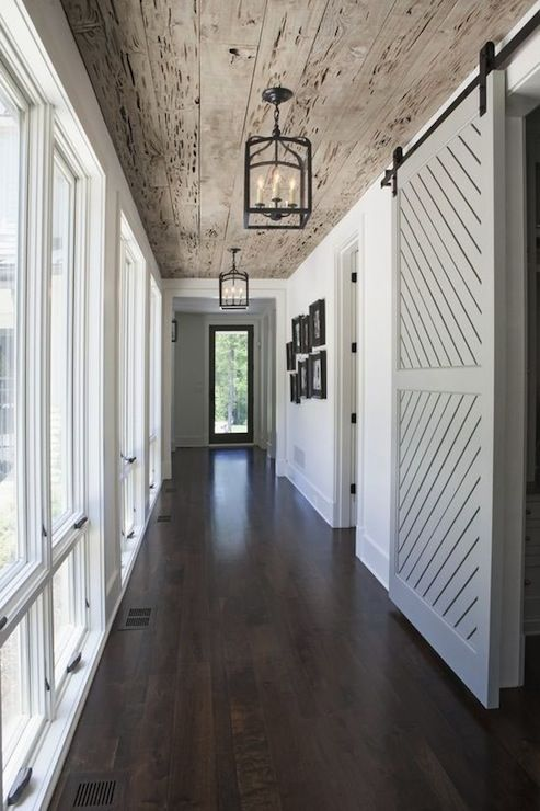 Wood plank ceilings, barn door, lantern light fixtures, dark floors.