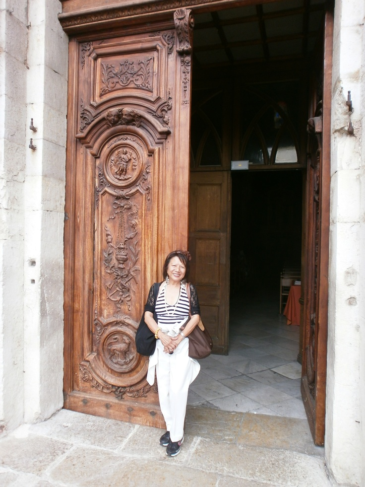 Adelina in front of the Cathedral of Grasse. The carved walnut wood doors which show the symbols of the four evangelists date back to 1721.
